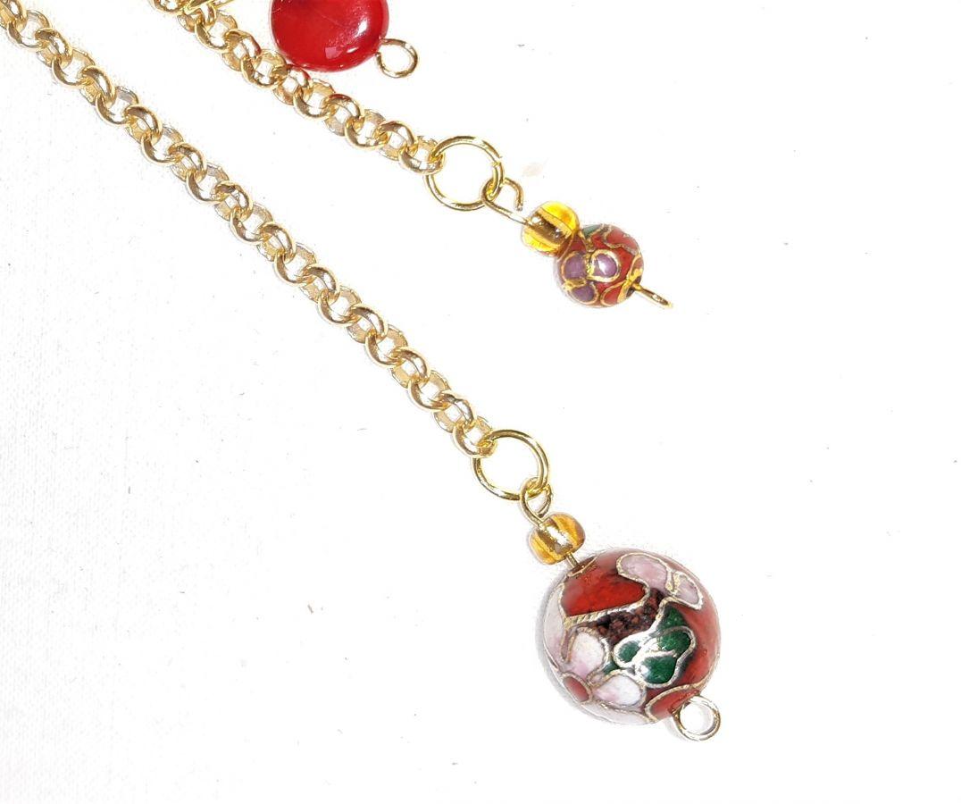 Bijou de sac pompon cuir de chèvre coloris rouge et perles cloisonnées.
